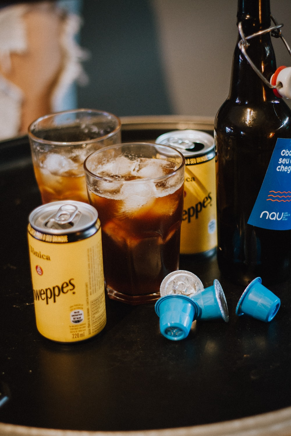 two yellow cans with drinking glasses on black table