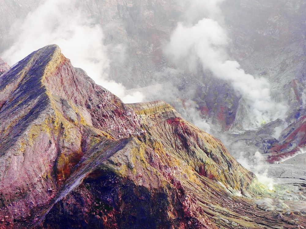 green and brown mountain under foggy weather during daytime