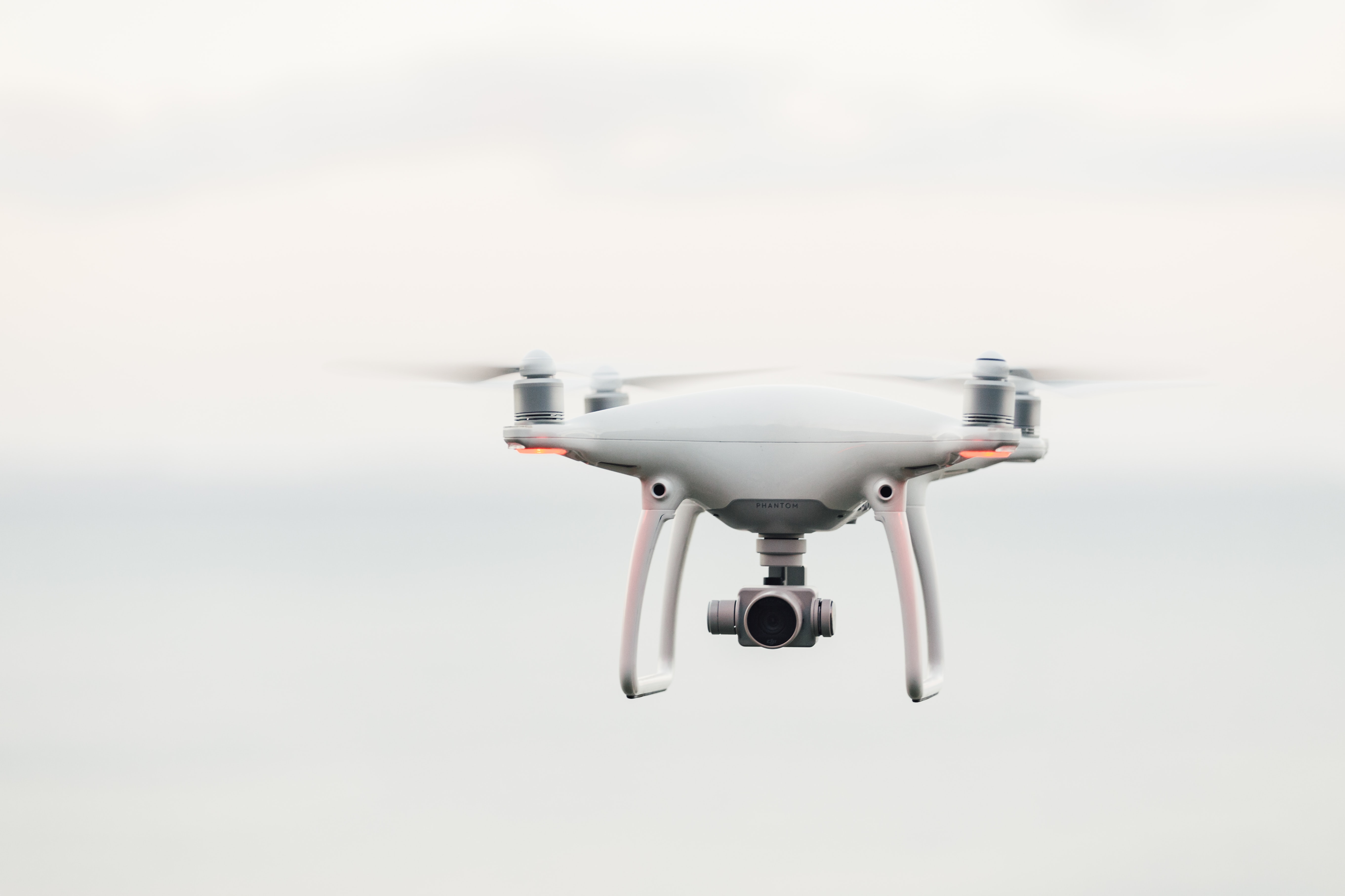 white quadcopter drone flying