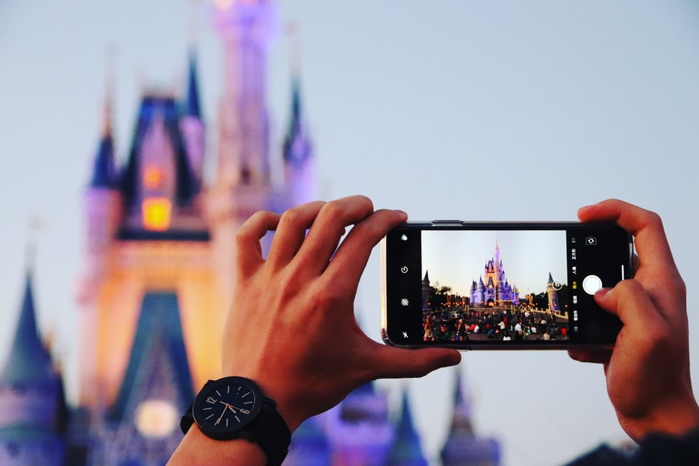 person taking photo a castle using smartphone