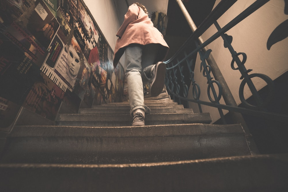 woman in pink jacket on stairs
