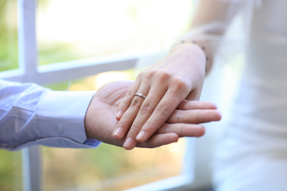 selective focus photography of man holding women's right hand with ring