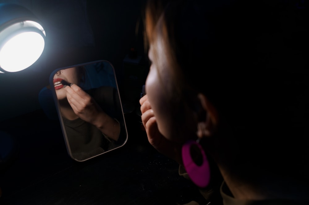 woman facing the mirror putting lipstick on the lips