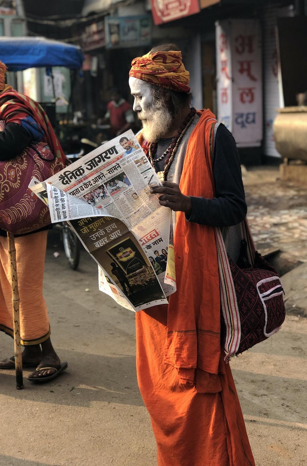 man reading newspaper beside street