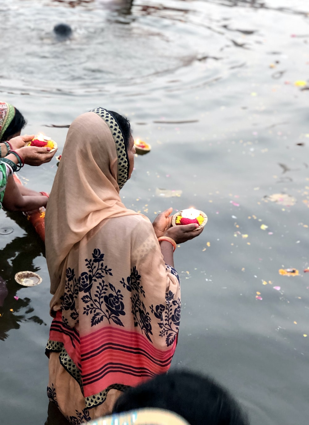 woman wearing pink hijab holding candle while standing on body of water
