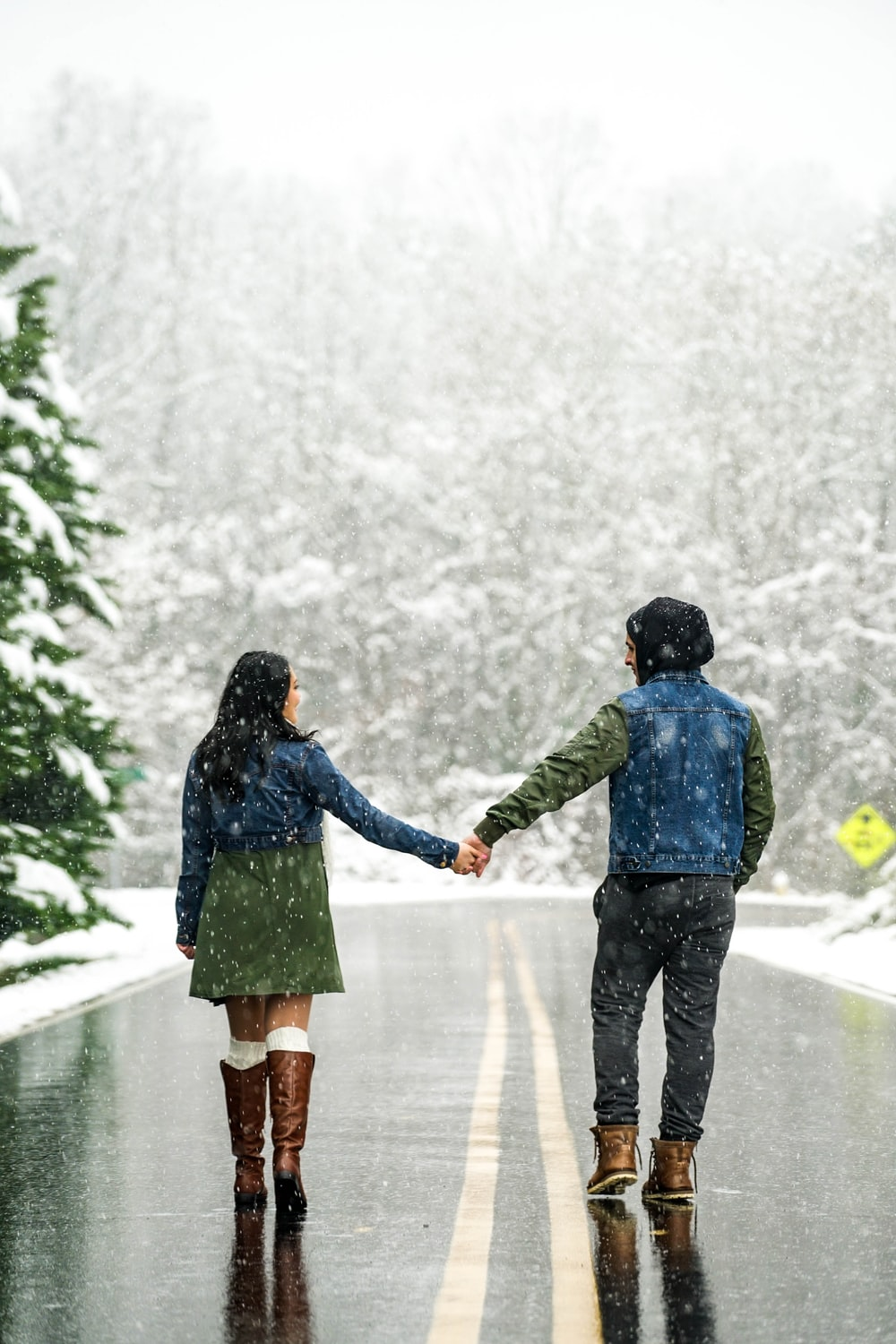 couple holding hands on wet road during daytime