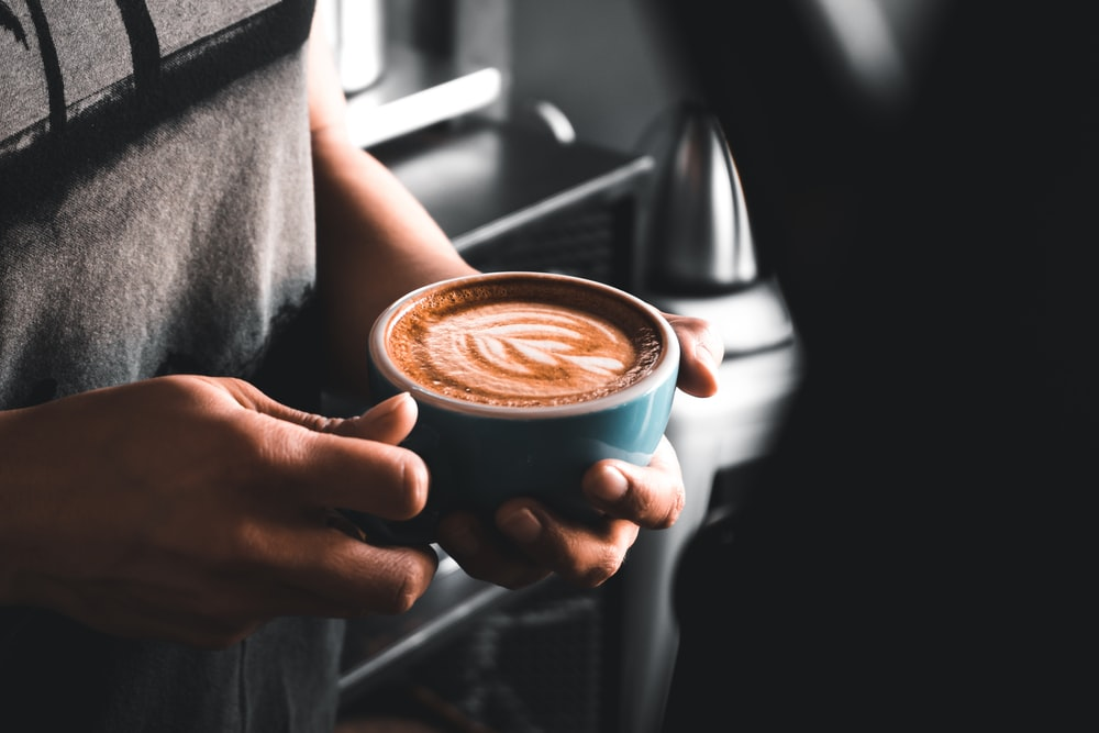 person holding cup of coffee close-up photography