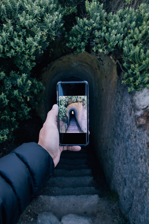 person taking photo of concrete cave