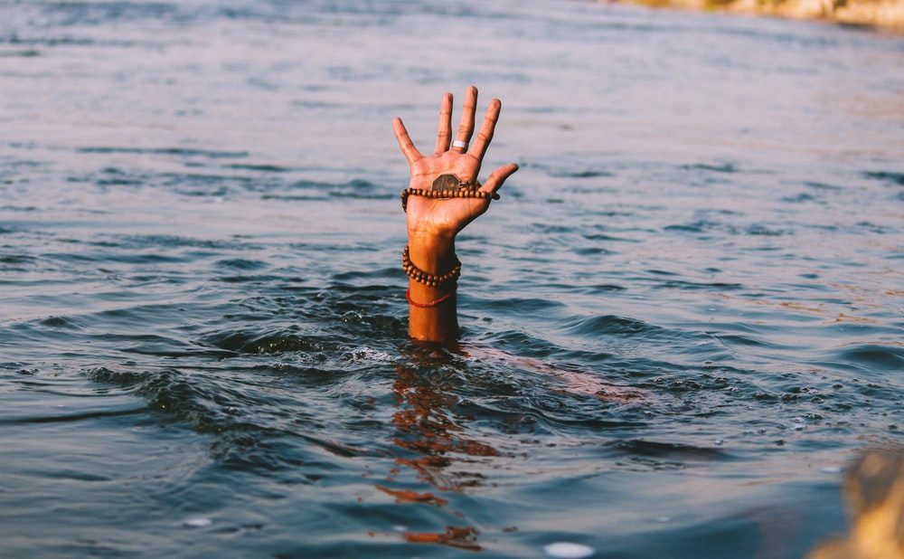 person underwater raising right hand