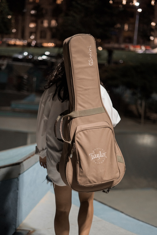 woman carrying brown Taylor guitar bag outdoor