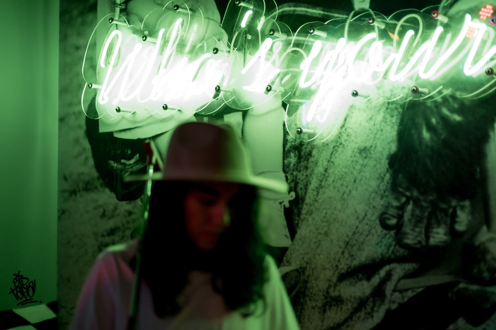 woman wearing hat with Who's Your LED signage