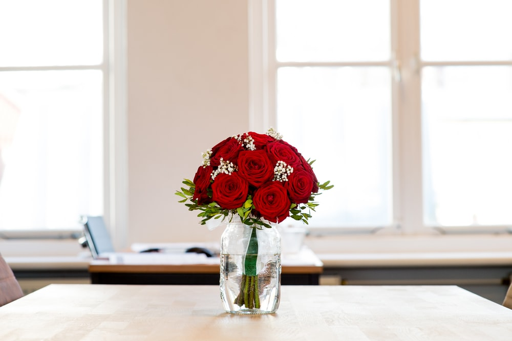 red roses on the glass vase on top of table
