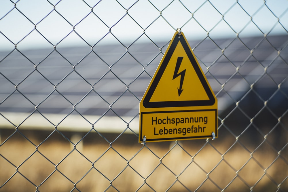 selective focus photography of danger high voltage signage on chain-link fence