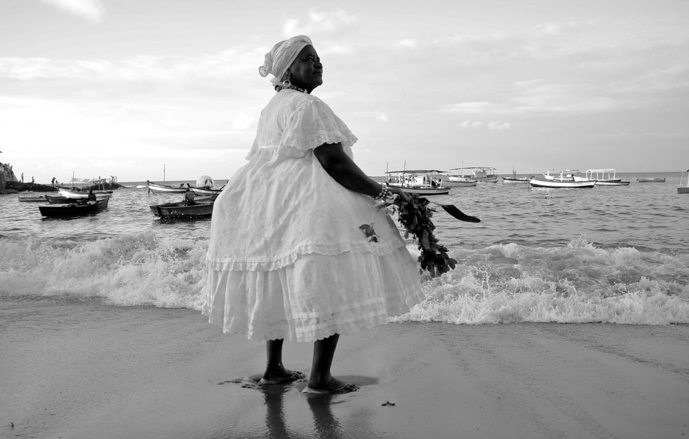grayscale photo of woman standing in front of seashore