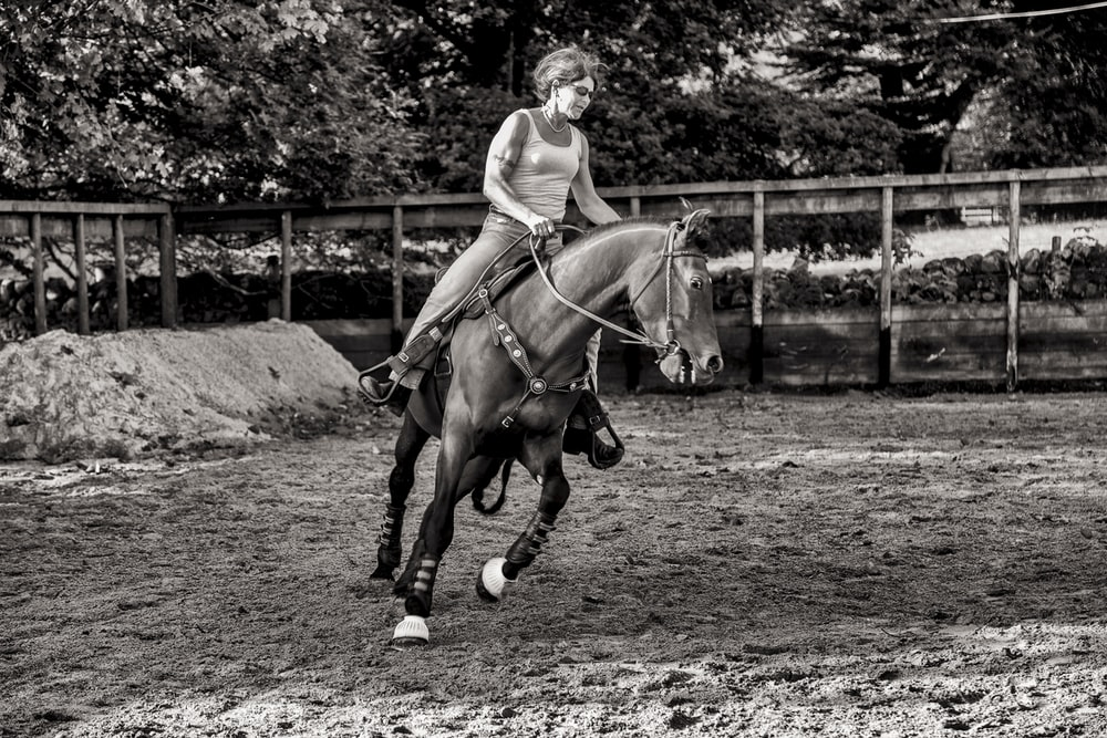 grayscale photography of woman riding horse