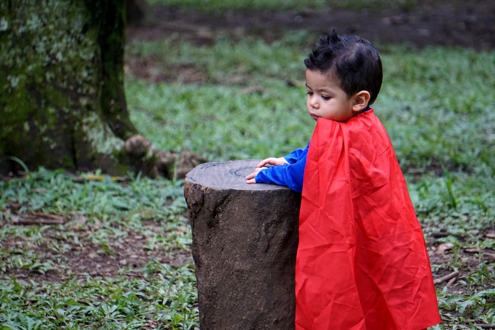 shallow focus photo of boy wearing red cape