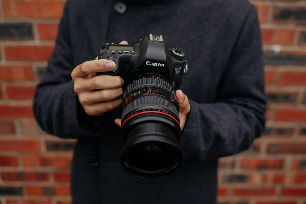 shallow focus photo of person holding black Canon DSLR camera