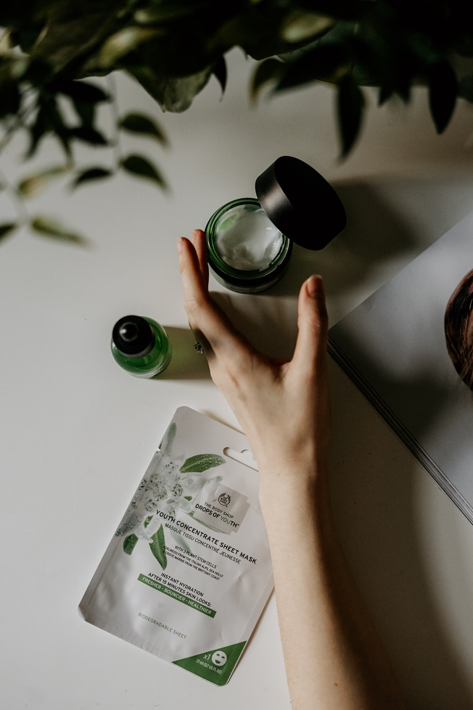 person touching black plastic bottle