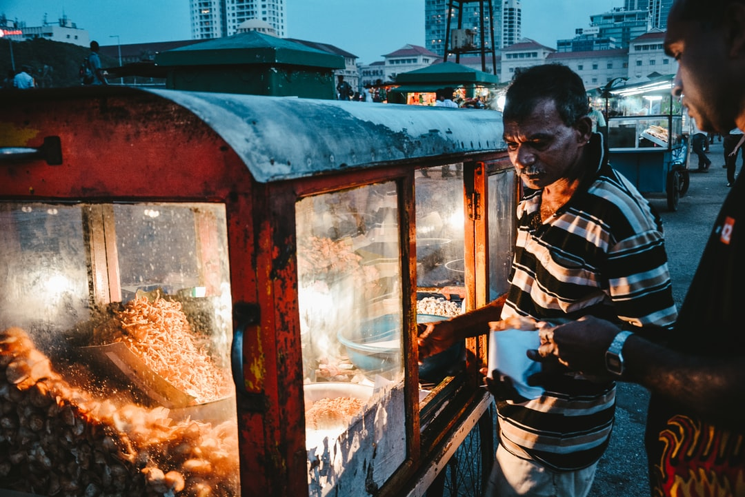 A man buying food from a street vendor operating a food stall  in Colombo, Sri Lanka. Not exactly sure what the food was called but it was delicious
