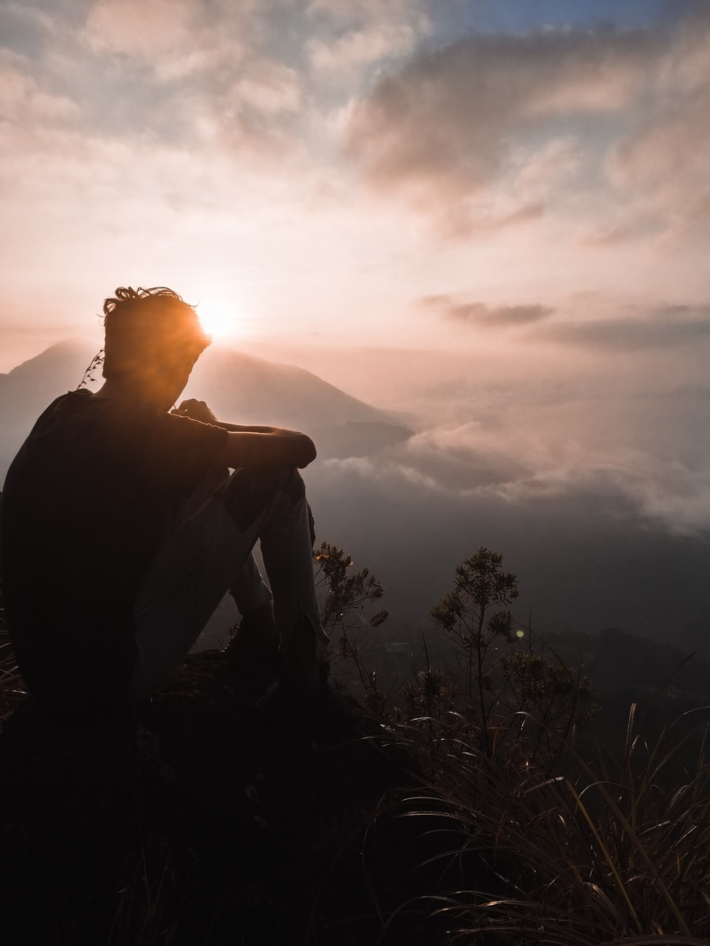 silhouette of man sitting during sunset