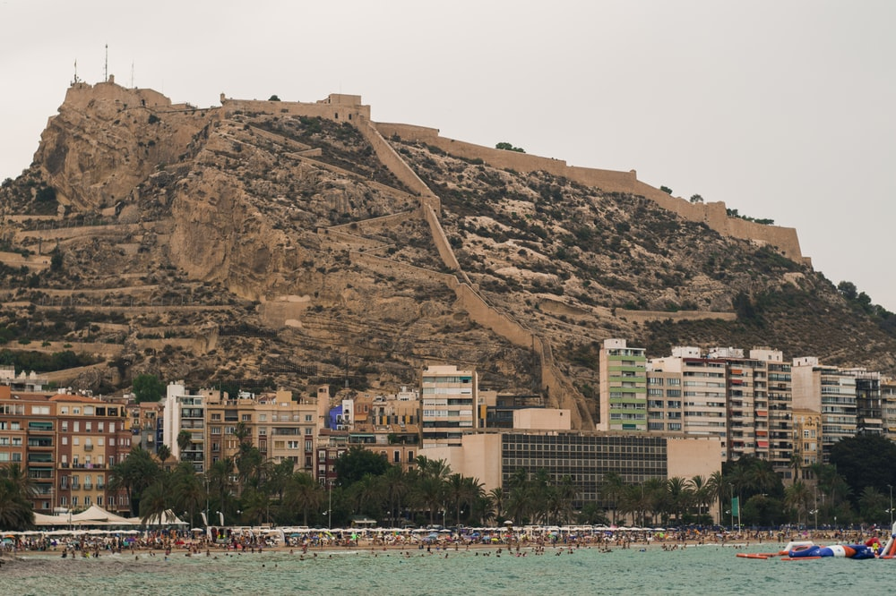 people in beach near buildings and mountain