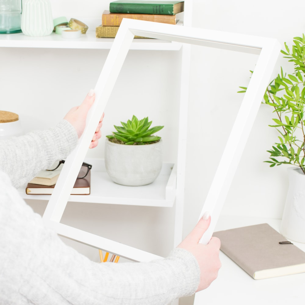 person holding white wooden frame
