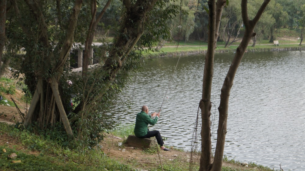 man wearing green dress shirt fishing
