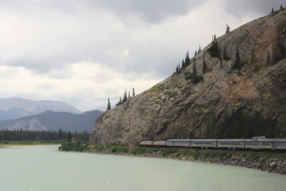 train passing near hill and body of water