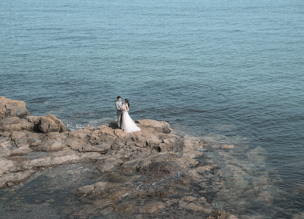 couple standing on rock during daytime