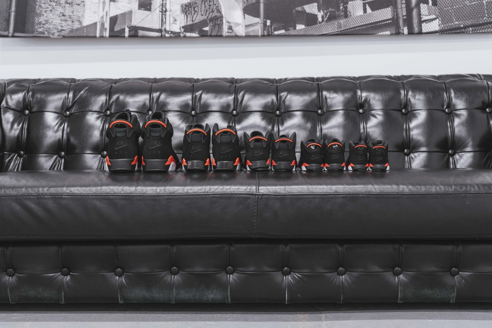five pairs of assorted-size black shoes on tufted black leather sofa