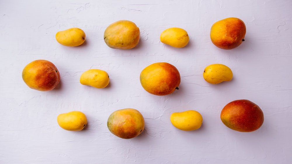 yellow and red fruits on white surface