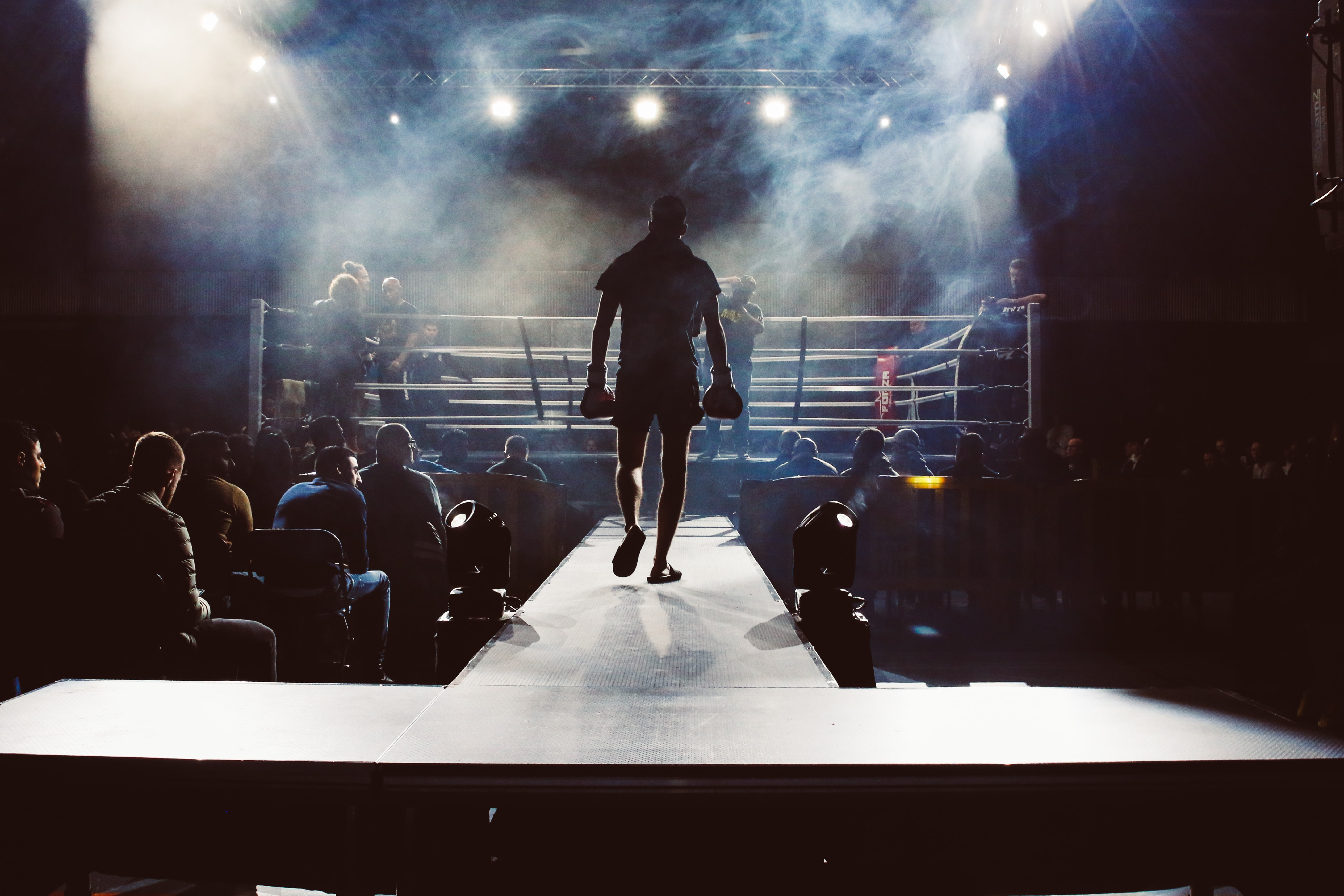 man standing and walking going on boxing ring surrounded with people