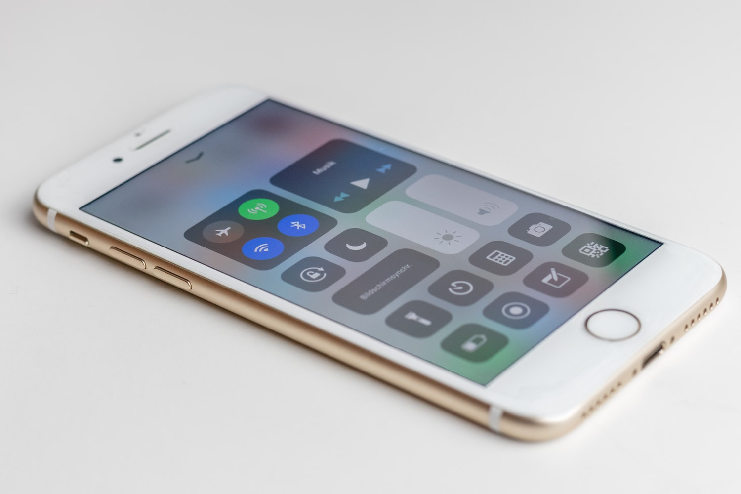 Gold iphone on white surface