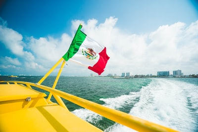 mexico flag on yellow boat cancun teams background