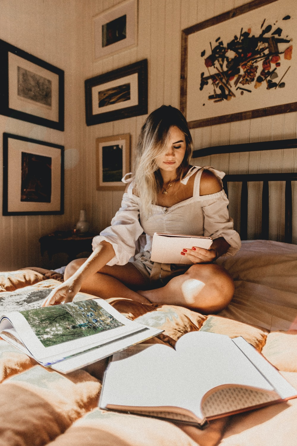woman sitting on bed holding books