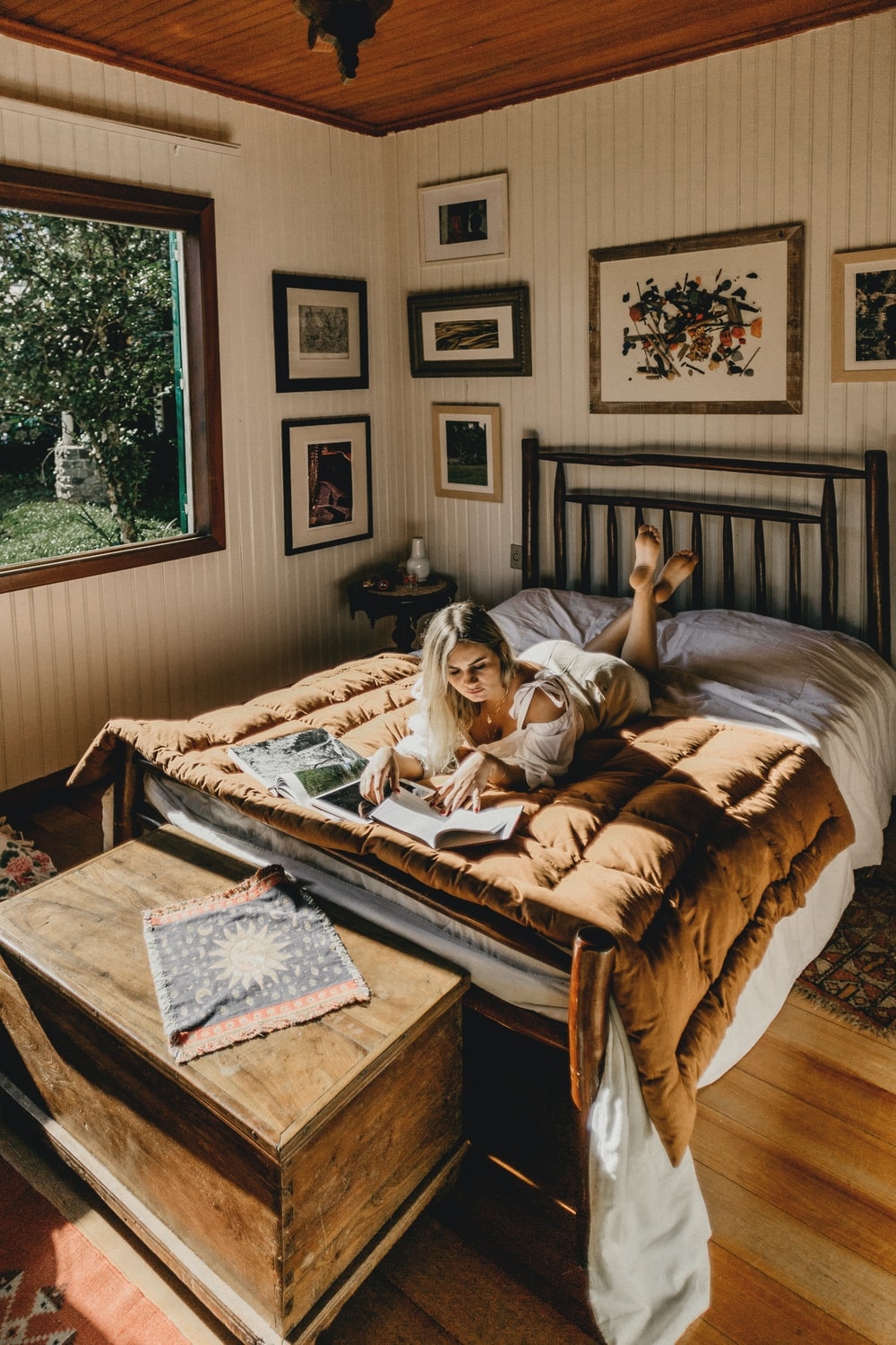 woman lying on bed while reading book