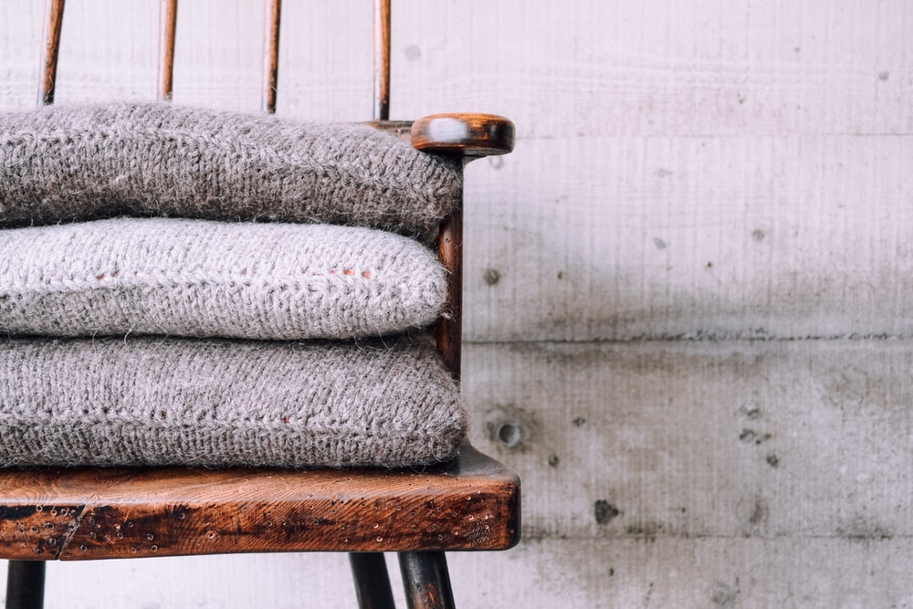 three gray knitted throw pillows on brown wooden armchair
