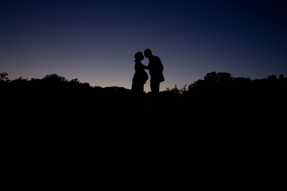 silhouette couple standing during golden hour