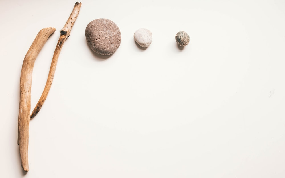three brown stones on white surface