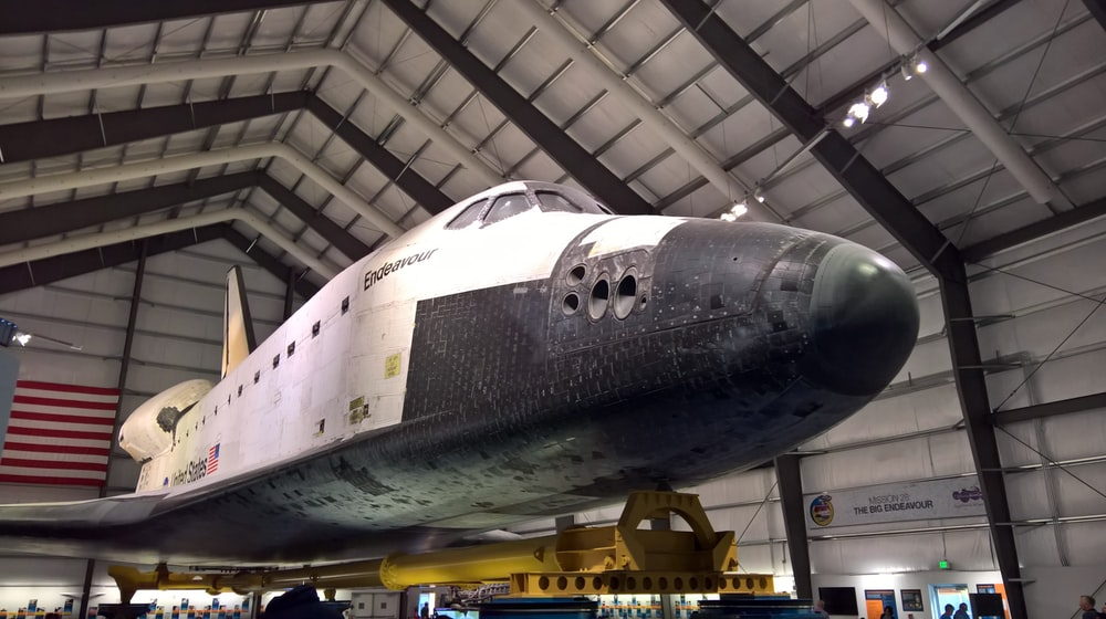 white and gray plane inside gray shed