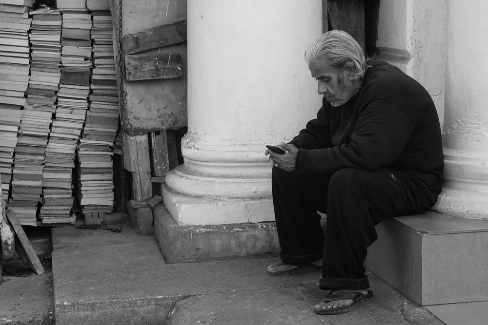 man sitting by the pillar while using smartphone