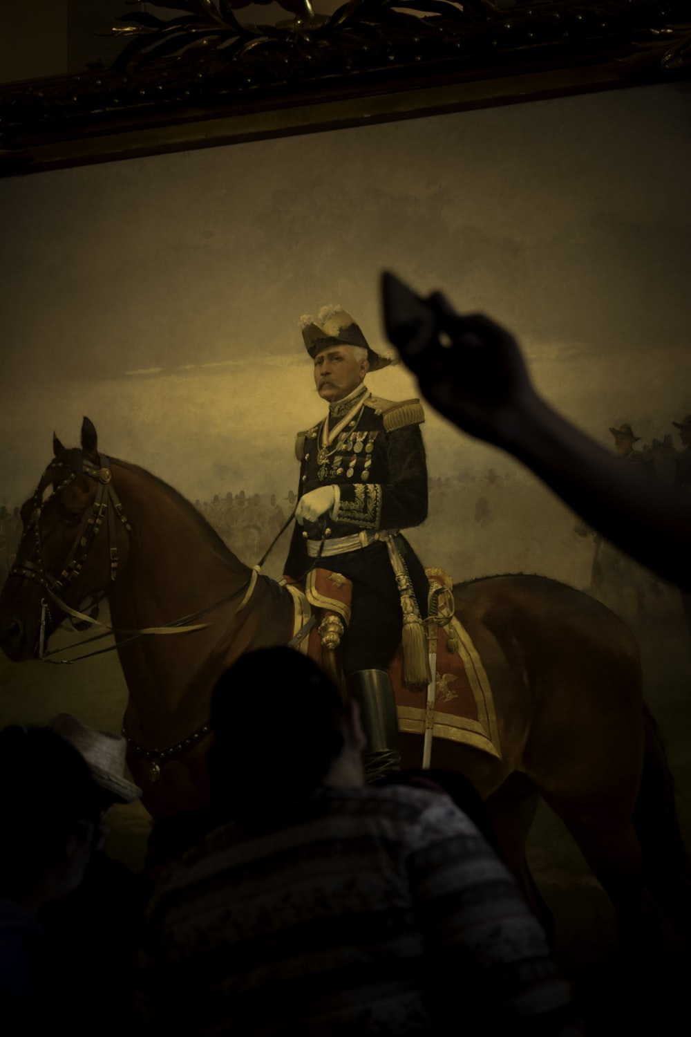 person looking at man in military uniform riding horse painting