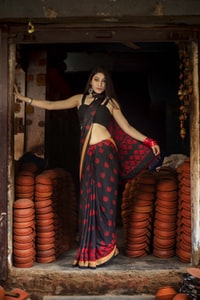 woman wearing red and black saree dress standing near brown clay pots