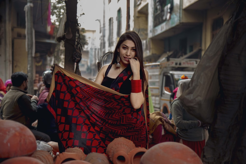 woman standing holding red and black textile near people and vehicles