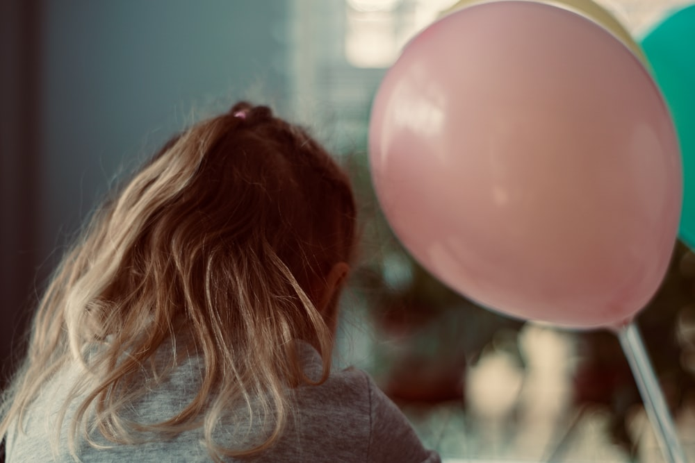 girl in gray shirt beside pink balloon
