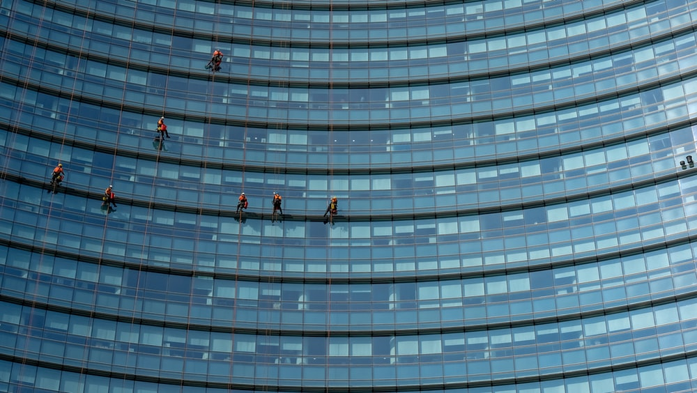people hanging on glass building