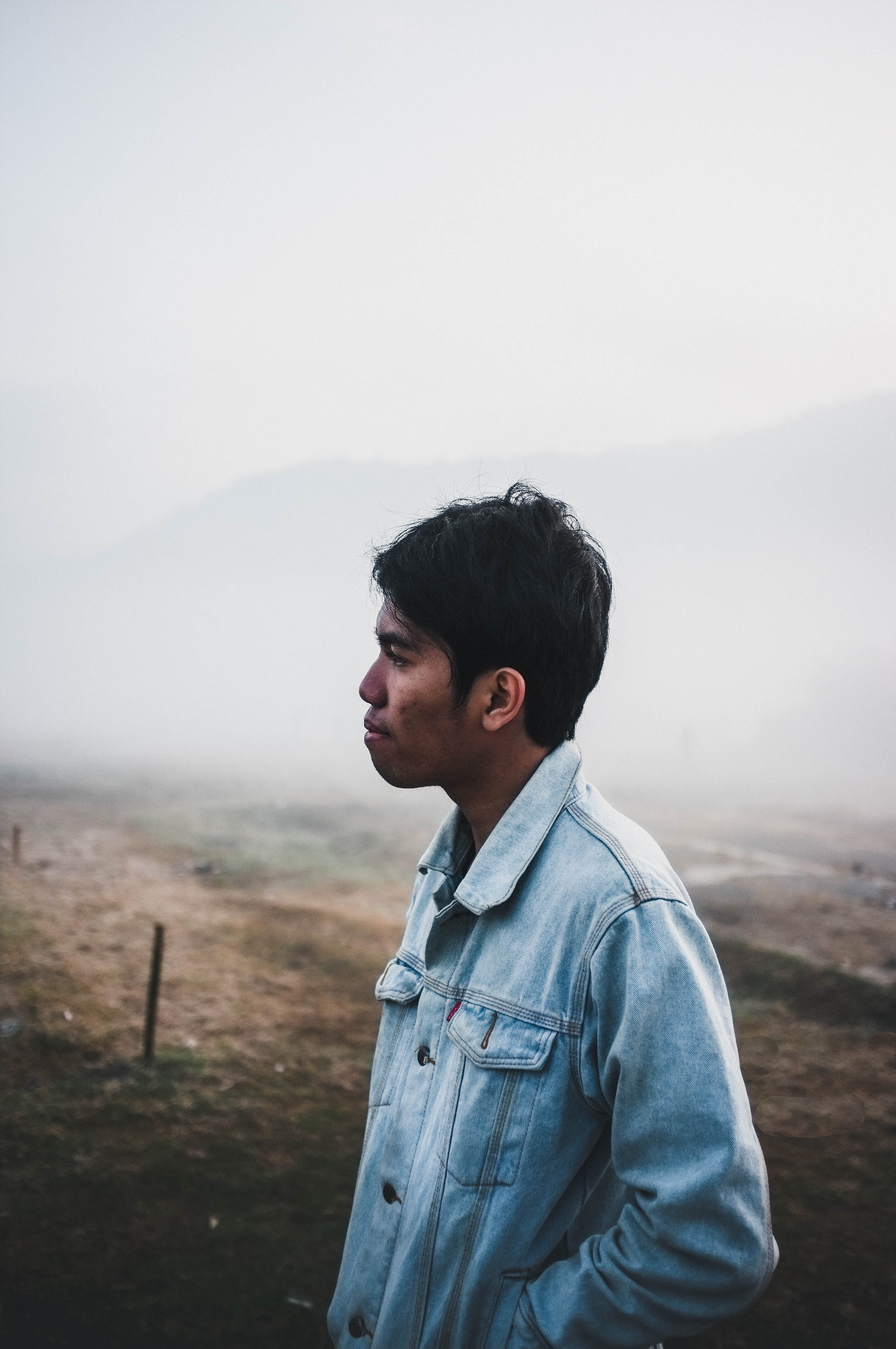 man wearing blue denim jacket under foggy weather