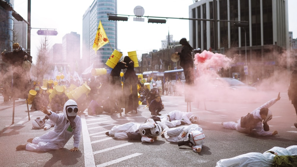 people wearing scrub suits lying on road covered with smoke