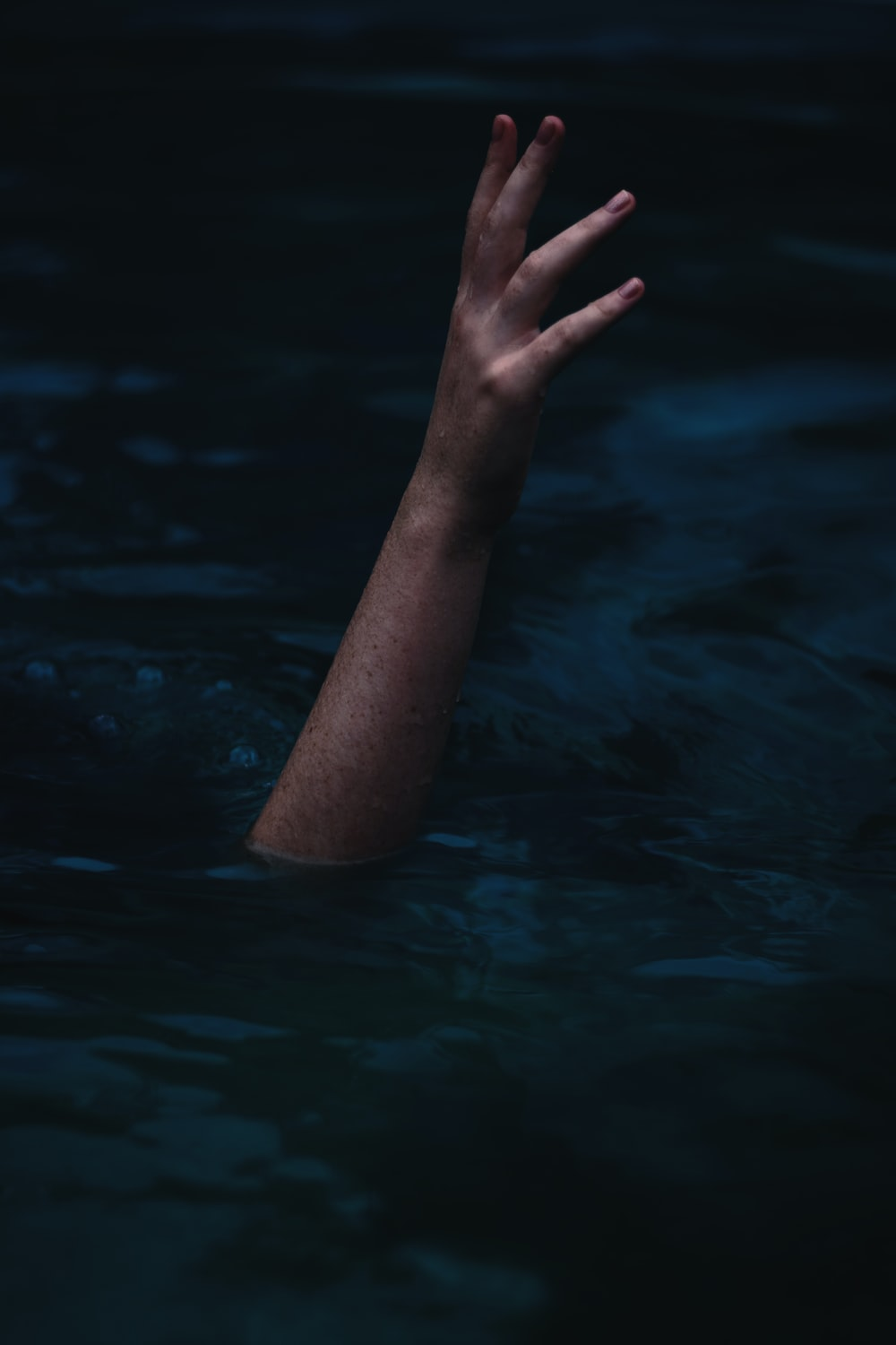 person showing right hand from body of water