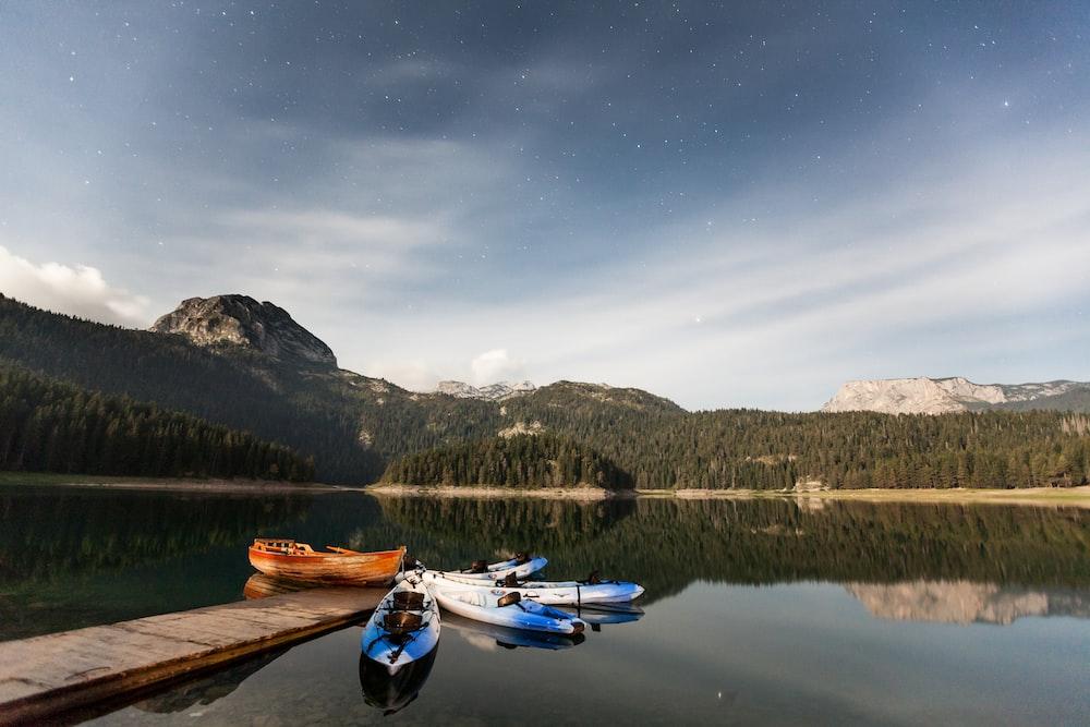 group of kayaks beside wooden dock
